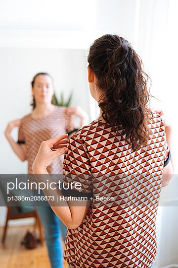 Frau betrachtet sich im Spiegel - p1396m2086873 von Hartmann + Beese