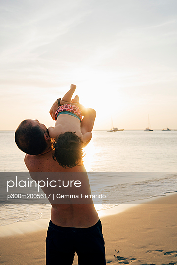 Thailand, Koh Lanta, father playing with his little daughter on the beach at sunset - p300m2005617 by Gemma Ferrando