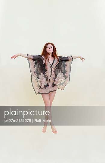 Woman floating against white background - p427m2181275 by Ralf Mohr