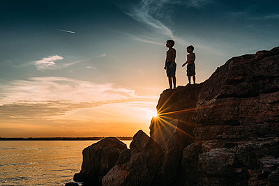 Low angle view of shirtless brothers standing on rocks by river against sky during sunset - p1166m1509393 by Cavan Images