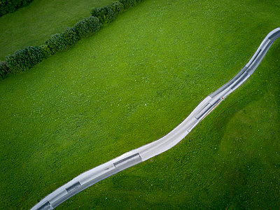 High angle view of road by grassy field - p1166m1530494 by Cavan Images
