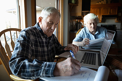 Senior couple paying bills at laptop in kitchen - p1192m2040235 by Hero Images