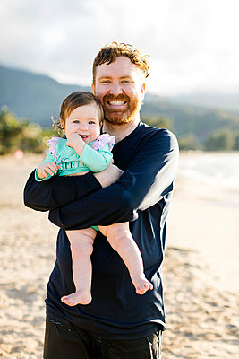 Man holding baby daughter on beach - p1427m2109767 by Jessica Peterson