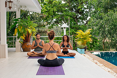 Two women and a man practicing yoga at the poolside - p300m1587686 by Mosu Media