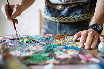 Male artist mixing oil paint on palette in artists studio, close up of hands - p429m1547671 by Arno Images