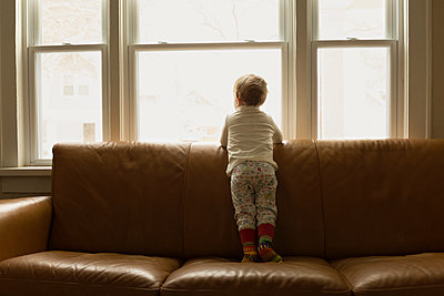 Caucasian boy looking out living room window - p555m1410881 by Roberto Westbrook