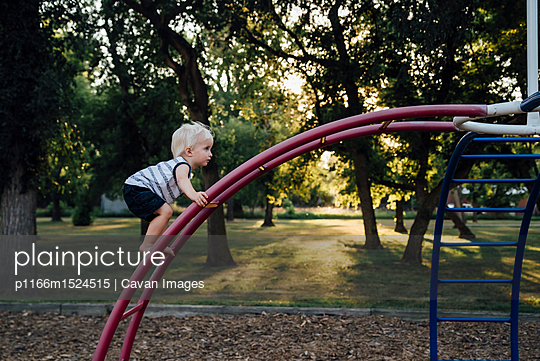Side view of baby boy climbing monkey bars at playground - p1166m1524515 by Cavan Images
