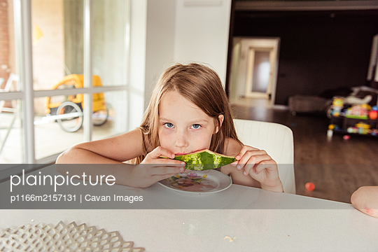 Little girl eating a watermelon - p1166m2157131 by Cavan Images
