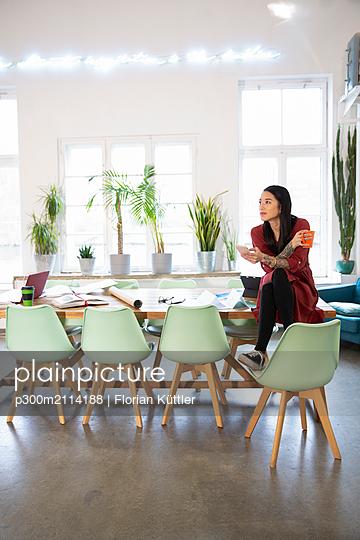Woman sitting on table in modern office - p300m2114188 by Florian Küttler