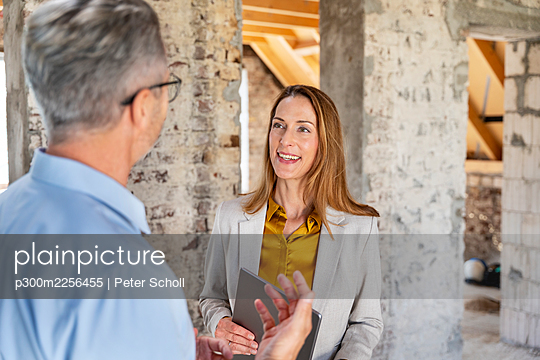 Engineer explaining to businesswoman while standing at construction site - p300m2256455 by Peter Scholl