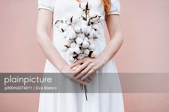 Woman with bunch of cotton plant standing in front of pink wall - p300m2274011 by Eva Blanco