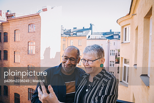 Senior couple taking selfie through mobile phone in balcony - p426m2238249 by Maskot