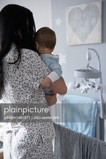 Caucasian mother holding baby son near crib - p555m1481971 by JGI/Jamie Grill