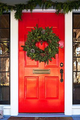 Christmas wreath hanging on red door - p1166m969228f by Cavan Images