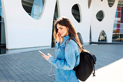 Spain, Barcelona, smiling young woman with backpack listening music with cell phone and earphones - p300m1587858 by Valentina Barreto
