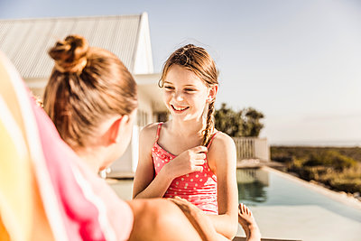 Portrait of happy girl with her mother at the poolside - p300m2167512 by Floco Images