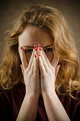 Young woman hiding face  - p794m899077 by Mohamad Itani