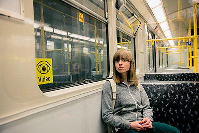 Junge Frau mit Rucksack sitzt in der U-Bahn - Spiegelung - p1212m1137018 von harry + lidy