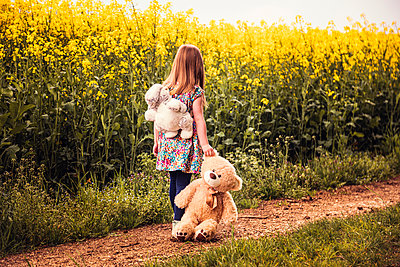 Girl walking alone with teddy and backpack on a field way - p300m2103853 by Sebastian Dorn