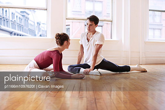 Young ballet dancers stretching in studio