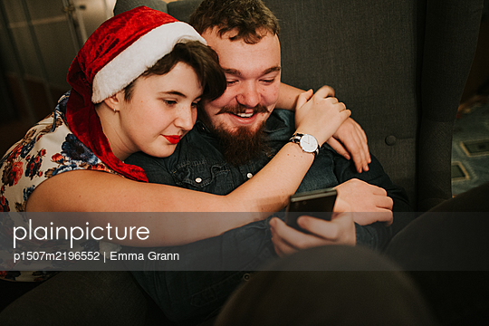 Teenage couple looks at smartphone in Christmas time - p1507m2196552 by Emma Grann