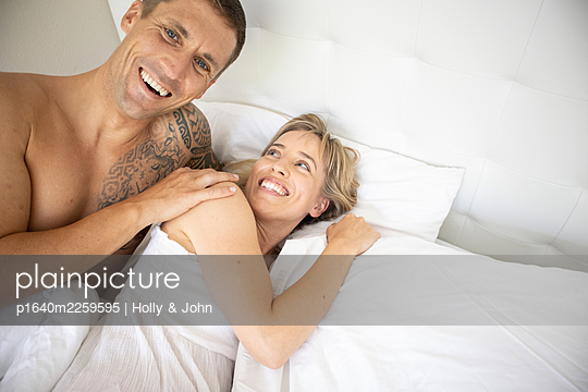 Couple in love embracing in bed - p1640m2259595 by Holly & John