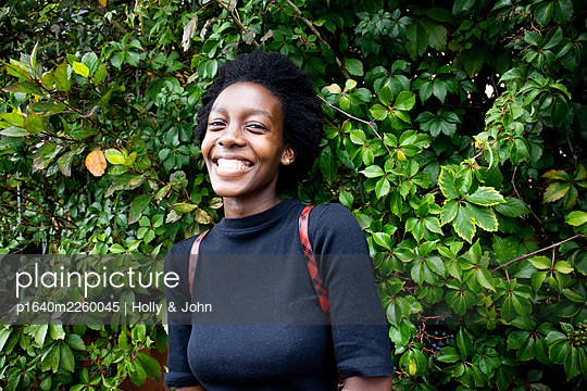 African woman between green leaves, portrait - p1640m2260045 by Holly & John