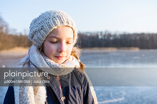 Germany, Brandenburg, Lake Straussee, portrait of a girl standing on frozen lake, eyes closed - p300m1581359 von Julia Otto