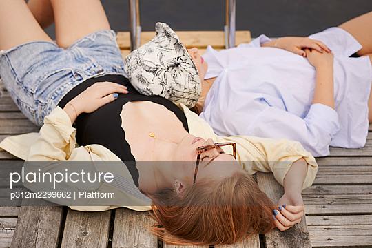 Two friends lying on pier - p312m2299662 by Plattform