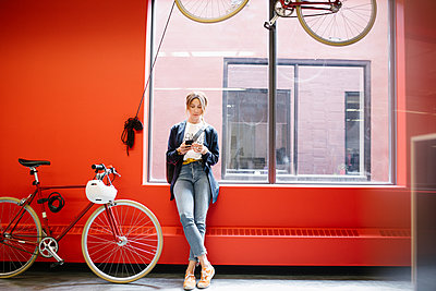Businesswoman with bicycle using smart phone at office window - p1192m2094876 by Hero Images