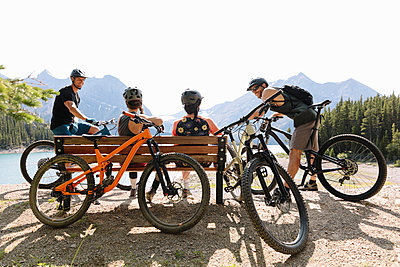 Friends taking a break from mountain biking at sunny lakeside - p1192m2129202 by Hero Images