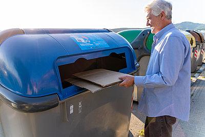 Senior man recycling cardboard in paper bank - p300m2113867 von VITTA GALLERY
