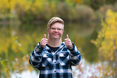 A young man with Down Syndrome giving a thumbs up in a city park on a warm fall evening: Edmonton, Alberta, Canada - p442m2154390 by LJM Photo