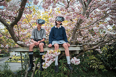 Mixed Race brother and sister sitting in tree wearing virtual reality goggles - p555m1219464 by Donald Iain Smith