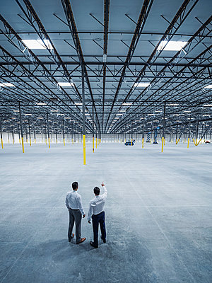 Businessmen talking in empty warehouse - p555m1305137 by Erik Isakson