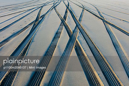 Tire tracks on the soft surface of sand on a beach.  - p1100m2085137 by Mint Images