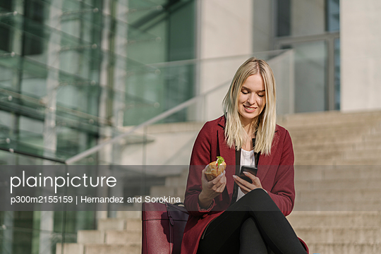 Blond businesswoman having a lunch outside and using smartphone - p300m2155159 by Hernandez and Sorokina
