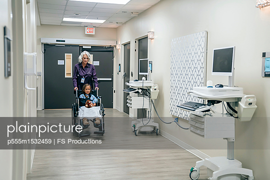 Doctor pushing girl in wheelchair - p555m1532459 by FS Productions