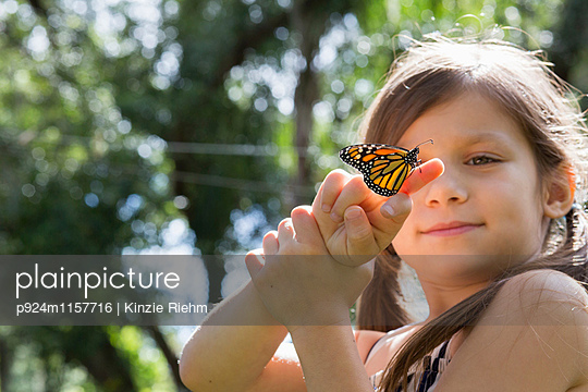 Girl holding monarch butterfly on finger - p924m1157716 by Kinzie Riehm