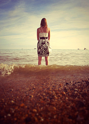 Young woman standing in the sea on Brighton Beach  - p1072m829419 by Neville Mountford-Hoare