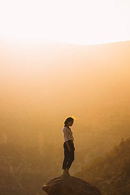 Side view of woman standing on rock against sky during sunset - p1166m1554312 by Cavan Images