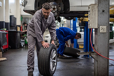 Car mechanics in a workshop changing tires - p300m1189155 by zerocreatives