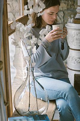 Woman sitting on window sill at home drinking tea - p300m2102740 von Alberto Bogo