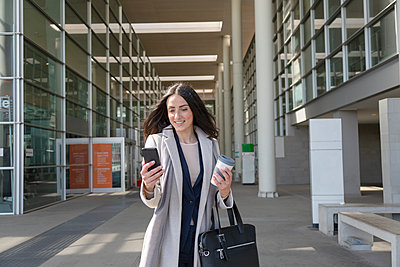 Young female entrepreneur using mobile phone while standing on footpath - p300m2281710 by Emma Innocenti