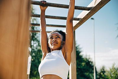 Female athlete hanging on monkey bar in park - p426m2270820 by Maskot