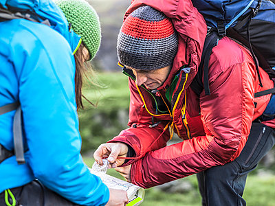 Hikers using map and compass - p429m765316 by Julian Love