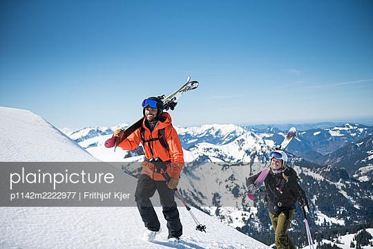 Zwei Skifahrer beim Aufstieg mit Skiern über der Schulter - p1142m2222977 von Frithjof Kjer