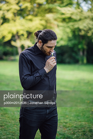Young man, dressed in black, standing in park, smelling flower - p300m2012636 von Jonathan Schöps