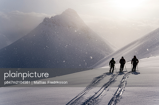 Three people ski touring near Grovfjord in northern Norway. - p847m2104981 by Mattias Fredriksson