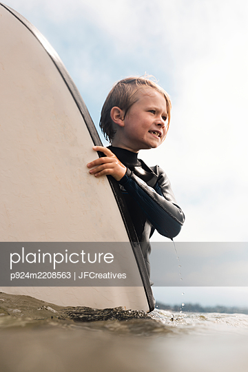 Portrait of young boy wearing wet suit, carrying surfboard into ocean, Santa Barbara, California, USA. - p924m2208563 by JFCreatives